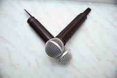 Zwei silberne Mikrophone lokalisiert über weißem Hintergrund Zwei drahtlose Mikrophone auf dem Konferenztische stockbild