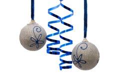 Zwei silberne Weihnachtskugeln mit lockigem Farbband Stockfotos