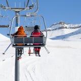 Zwei Skifahrer auf Sessellift und schneebedeckter Skisteigung Stockfotos