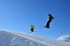 Zwei Skifahrer, die zusammen springen lizenzfreies stockfoto