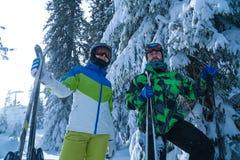 Zwei Skifahrer ein Mann und ein Frauenstand mit Ski fahrenden Ferien in den Bergen stockfotos