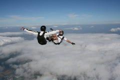 Zwei Skydivers in sitzen bringen während im freien Fall in Position Stockfotografie