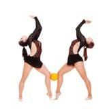 Zwei smiley Gymnasts, die mit gelber Kugel aufwerfen Stockfoto