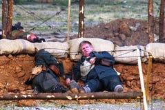 Zwei Soldaten-reenactors legen aus den Grund, eins von ihnen Blicke auf Kamera Stockfotos
