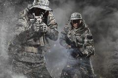Zwei Soldatmänner der besonderen Kräfte, die ein Maschinengewehr auf dunklem Hintergrund halten lizenzfreie stockfotos