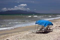 Zwei Sonnenbetten auf einem leeren Strand Lizenzfreie Stockfotos