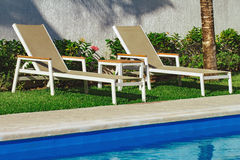 Zwei Sonnenruhesessel durch das Pool Lizenzfreie Stockbilder