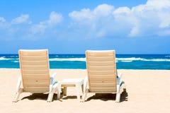 Zwei Sonnestrandstühle auf Küste nahe Ozean Stockbilder