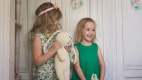 Zwei spielerische nette Mädchen, die mit dem angefüllten Kaninchen stehen stock video