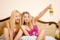 Zwei spielerische nette sexy blonde Mädchen in den rosa Pyjamas, die Spaß im Schlafzimmer haben Lizenzfreie Stockbilder