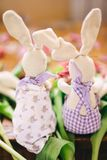 Zwei Spielzeughasen sitzen auf den Blumen Rückseitige Ansicht handarbeit Junges Küken in Wanne, 2 malte Eier und Blumen lizenzfreie stockfotos