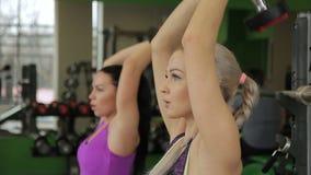 Zwei Sportlerinnen tun Sitztrizeps, den Dummkopf moderne Turnhalle eindrücken stock video