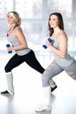 Zwei sportliche junge Frauen, die Aerobic mit Dummköpfen tun Stockfotos