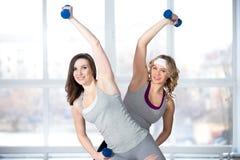 Zwei sportliche junge Frauen, die Aerobicpraxis mit Dummköpfen haben lizenzfreies stockfoto