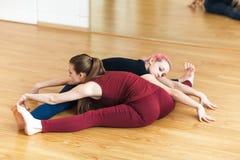 Zwei sportliche Mädchen in der Turnhalle, die acroyoga, Yoga mit Partner, Weitwinkelsitzrumpfbeuge, Upavishtha Konasana tut Stockfoto