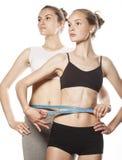 Zwei Sportmädchen, die sich messen, lokalisierten auf Weiß stockfoto