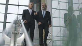 Zwei sprechende leitende Angestellten beim Abstieg der Treppe Stockbild