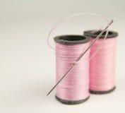 Zwei Spulen rosafarbenes Gewinde mit Nadel Stockfotografie
