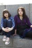 Zwei städtische jugendlich Mädchen, die auf Treppen sitzen lizenzfreie stockfotos