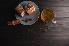 Zwei Stücke des vielschichtigen Honigkuchens auf einer Platte, auf einem schwarzen hölzernen Hintergrund mit einer Tasse Tee, Ess lizenzfreie stockbilder