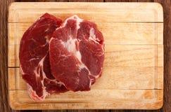 Zwei Stücke Fleisch auf einem hölzernen Brett Stockfoto