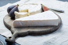 Zwei Stücke französischer Frischkäse Briekäse und Camembert mit weißer Form und starkem Geruch, dienten mit frischen reifen Feige stockbild