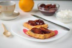 Zwei Stücke gebratenes französisches Brot auf einer weißen Platte auf einem Holztisch Stockbilder
