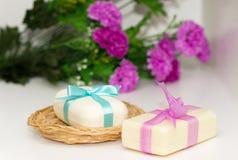 Zwei Stücke Seife mit einem Korb mit einem Bogen und Blumen Lizenzfreie Stockbilder