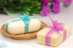 Zwei Stücke Seife mit einem Korb mit einem Bogen und Blumen Stockbild