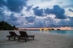 Zwei Stühle auf dem maledivischen Strand bei schönem Sonnenuntergang stockbild