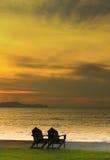 Zwei Stühle auf dem Strand mit Sonnenuntergang Stockfotos