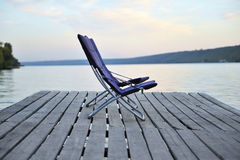 Zwei Stühle auf einer hölzernen Plattform auf dem Fluss stehen still Stockbild