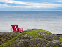 Zwei Stühle, die Ozeanufer übersehen Lizenzfreie Stockfotografie
