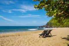 Zwei Stühle im Ufer eines Strandes an einem sonnigen Tag Lizenzfreie Stockfotos