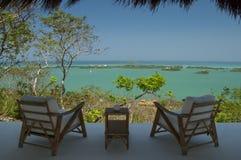 Zwei Stühle mit grünem karibischem Wasser stockfotos