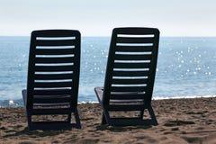 Zwei Stühle stehen auf Strand nahe Meer Stockfotografie