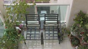 Zwei Stühle und ein Garten auf einem Balkon stock video footage