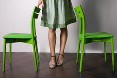 Zwei Stühle und Frauenfahrwerkbeine stockfotografie