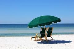 Zwei Stühle und Regenschirm auf weißem Sandstrand Lizenzfreies Stockbild