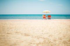Zwei Stühle und Regenschirm am Strand Stockbilder