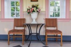 Zwei Stühle und Tabelle mit Blumenstrauß von Blumen im Vase auf einem Patio Lizenzfreies Stockbild