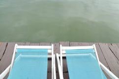 Zwei stützen Stühle auf dem Dock, das einen grünen See gegenüberstellt Stockbilder