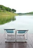 Zwei stützen Stühle auf dem Dock, das einen grünen See gegenüberstellt Stockfotografie