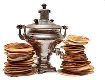 Zwei Stapel Pfannkuchen und Samowar an Stockbild