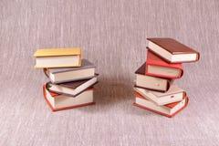 Zwei Stapel von kleinen Büchern auf einem Leinenhintergrund Stockbilder