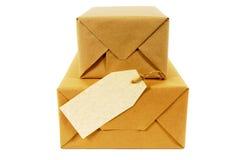 Zwei stapelten Pakete oder Pakete des braunen Papiers mit dem leeren Manila-Adressen-Etikett, das auf weißem Hintergrund lokalisi Lizenzfreie Stockfotos