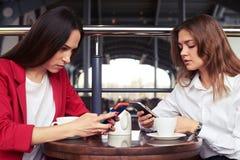 Zwei starke Geschäftsfrauen, die in den Smartphones arbeiten Stockfotos