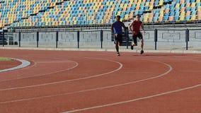 Zwei starke Rivalen, die am Stadion, schnell laufend konkurrieren und bereiten sich für Marathon vor stock video footage
