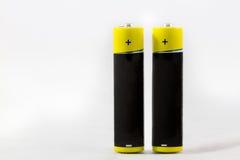 Zwei stehende gelb-schwarze alkalische Batterien AAA lokalisiert auf whi Lizenzfreies Stockfoto