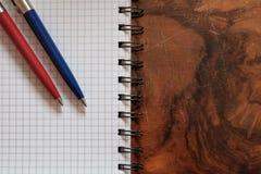 Zwei Stifte auf einem Kopienbuch lokalisiert auf hölzernem Hintergrund Stockbilder